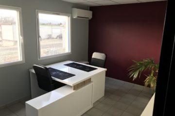 bureaux blancs. chaises noires. plante. espace de coworking.