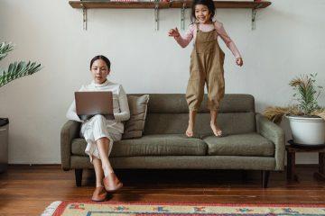 enfants et femme sur un canapé. la femme fait du télé-travail